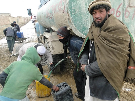 Without Running water, residents of AliceGhan que in the snow for water that is trucked in