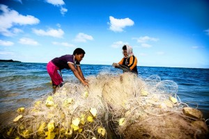 Fiji residents untwist a fishing net in Tobou, Fiji. Photo: Aurora Photos.
