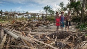 Children stand around the remains of a local community centre destroyed in cyclone Pam in Port Vila. Photo: New Zealand Defence Force/Getty Images.