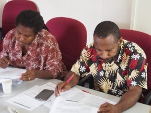 Denise Lokinap and Peter Kanaparo examine questionnaires during training