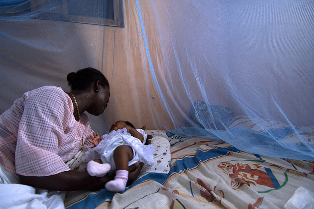 Mother places infant into a bed surrounded by a bed net in Ghana (Flickr/World Bank/Arne Hoel CC BY-NC-ND 2.0)