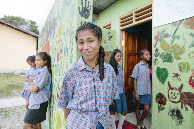 Etelvina Vita Da Costa, 15 (centre), outside the new toilet block at Ailuli Pre-Secondary School in Same, Manufahi District, Timor-Leste (WaterAid/Greenwood)