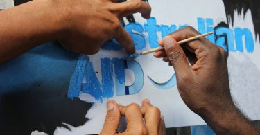 Painting the Australian Aid logo, Solomon Islands (Yvonne Green/DFAT/Flickr CC BY 2.0)