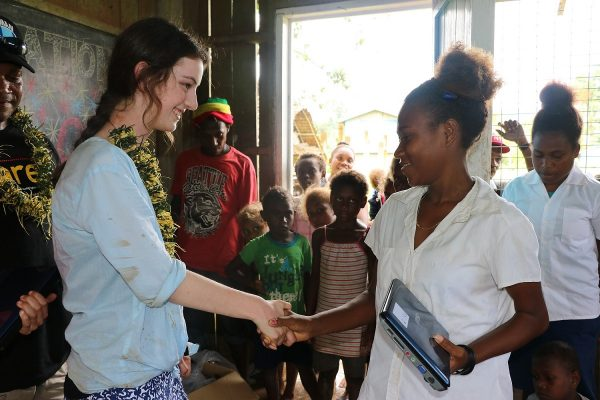 Grace presenting one of the donated laptops to the Head Girl of the One One Village Primary School, Malaita Province