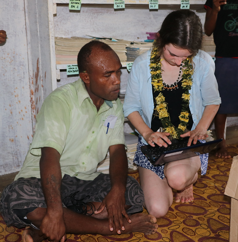 Grace showing a teacher from the One One Village School one of the laptops donated by the McCarthy children's school (The Scots PGC College in Warwick, Queensland)