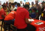 Digicel staff members register customers at a temporary stand while others wait, Port Moresby, December 2017 (Credit: Amanda H A Watson)