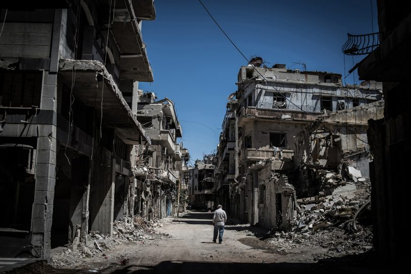 A Syrian refugee walks among severely damaged buildings in downtown Homs, Syria in 2014 (Pan Chaoyue/Flickr/CC BY-NC-ND 2.0)