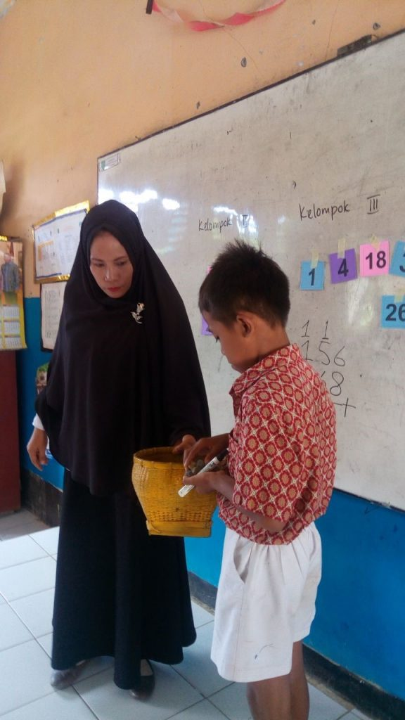 Ibu Rahmi from SDN Sila 1 now uses teaching aids she finds in her local community (in this case, small stones) during her numeracy class. By utilising physical, tangible examples that the learner is already familiar with, they can more easily make connections with the new ideas and skills that are taught, regardless of their Bahasa Indonesia fluency (Credit: INOVASI Program)