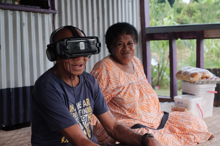 75-year old Rupeni Vatugata, with his wife Losena, watches their story unfold in 360-degree virtual reality (Credit: Tom Perry/World Bank)