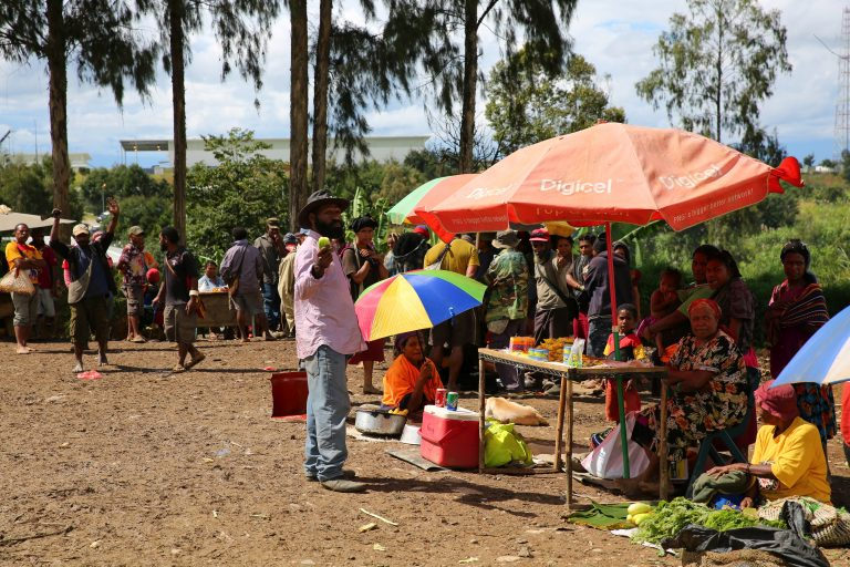 Landowners at Hides market with gas conditioning plant in background (Credit: Michael Main)
