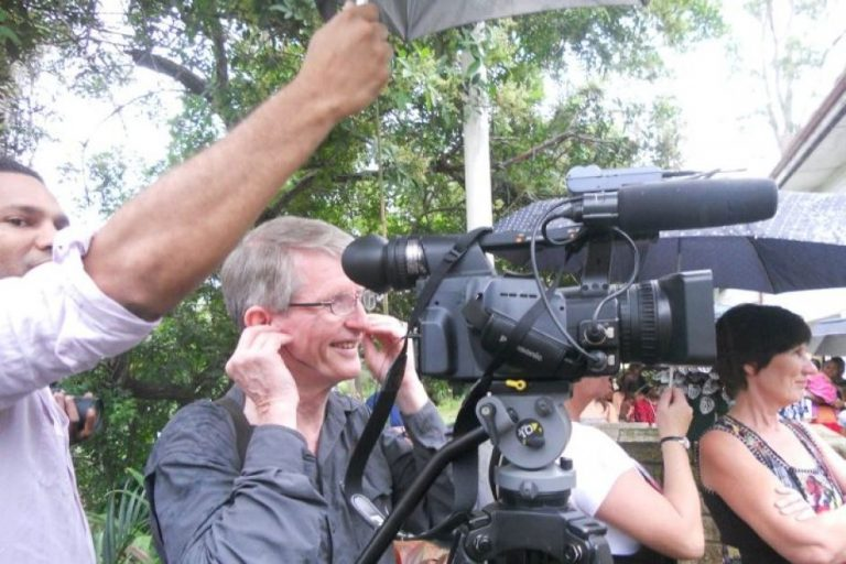 Sean Dorney filming at the opening of Jocelin Leahy's Pacific Art studio in 2014 (Credit: ABC)