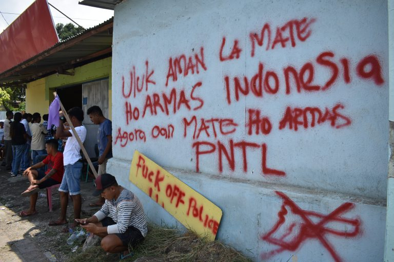 Young men hold vigil outside the homes of the victims' families, in front of anti-police graffiti that now covers the neighbourhood (Photo: Bardia Rahmani)