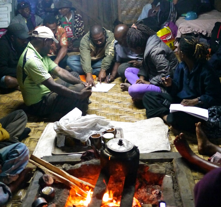 Community development workers from CARE PNG and the Community Development Agency (nightly debrief and reviewing plans during drought response, Gumine District, 2016)