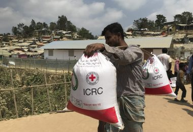 Man carrying two ICRC BRCS food bags (ICRC)