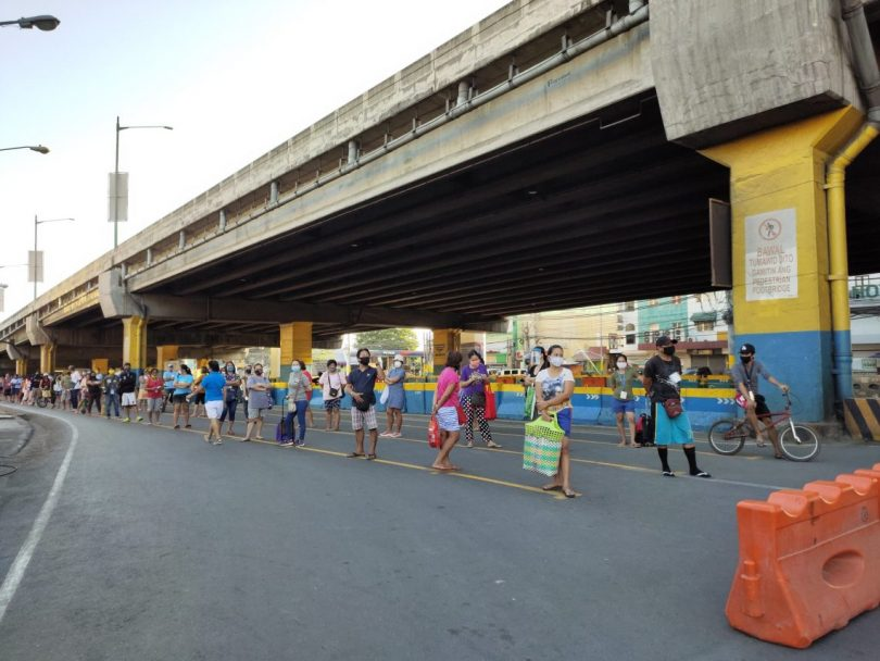 People keeping distance before entering the public market in Muntinlupa City, Philippines (ILO Asia-Pacific/Flickr CC BY-NC-ND 2.0)
