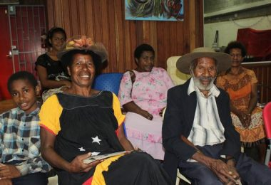 Third-born daughter, Nancy Kumanyal (in PNG meri blouse and hat), and Nepe Kumanyal (in Akubra hat) with other family members in the PNG National Museum Theatrette, August 2015.
