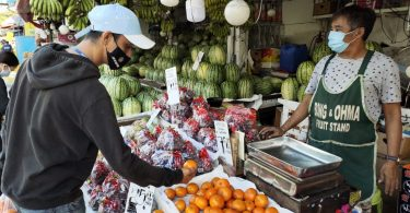 A customer and fruit seller keeping distance in the market, Manila (ILO Asia-Pacific)