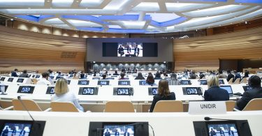 Photograph of a large conference room where all all delegates have a small video screen and headphones and all are looking at large screen with three people seated on stools.