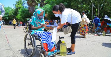 Emebet receiving support by way of food items from Almaz, a CBM partner organisation staff member in Ethiopia