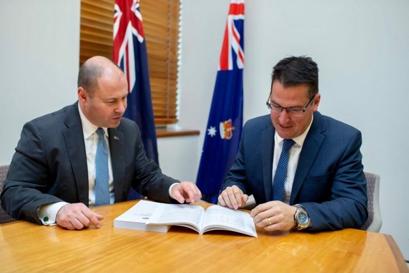 The Treasurer and Minister for International Development looking over the 2021 budget papers