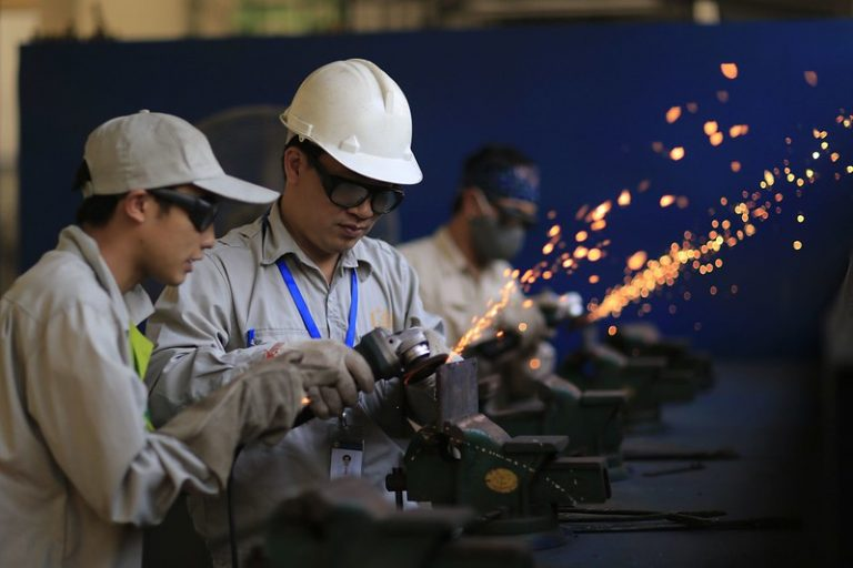 Photograph of migrant workers learning metal fabrication skills