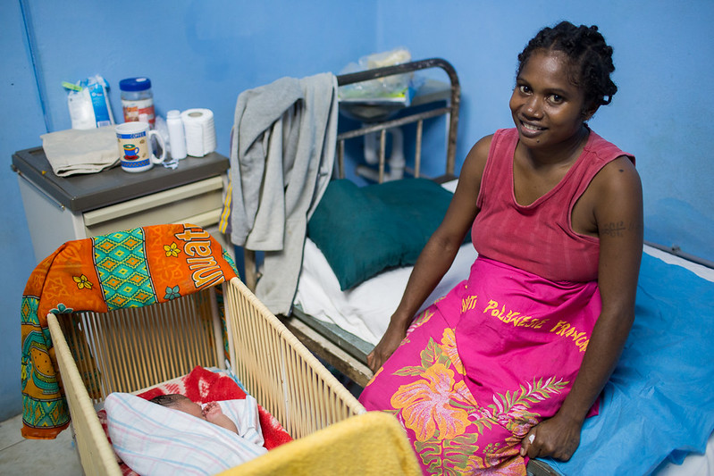 Photograph of a smiling mother sitting on a bed beside a cradles with a new-born baby