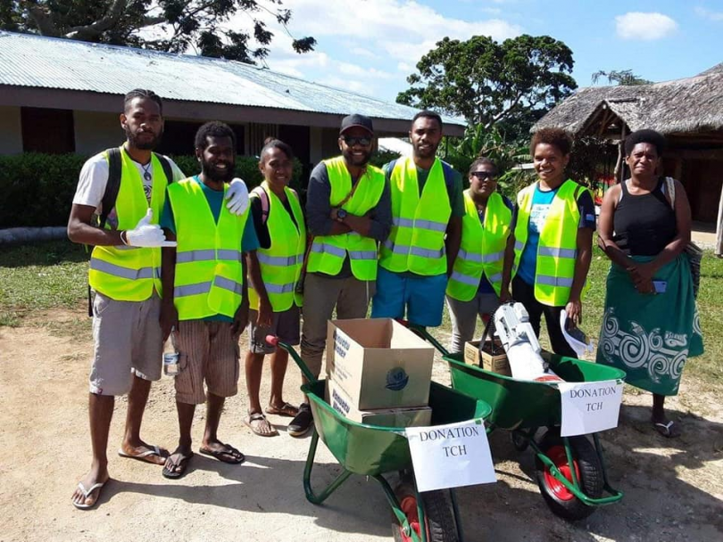 Photograph of group of eight ni-Vanuatu people in hi-vis vests with two wheelbarrows that have signs saying 'Donation TCH'.