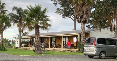 Photograph of a single story building with a verandah on which there are three people and some outdoor tables and benches. There are tall palm trees growing around the house and a small van parked in the driveway.