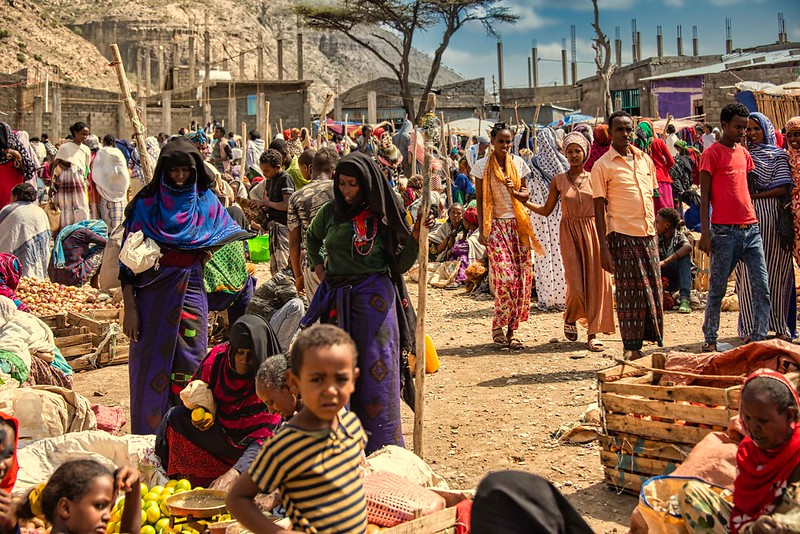 Photograph of an open air market in Ethiopia, with a crowd of people on dusty ground looking at fruit in large wooden bins.