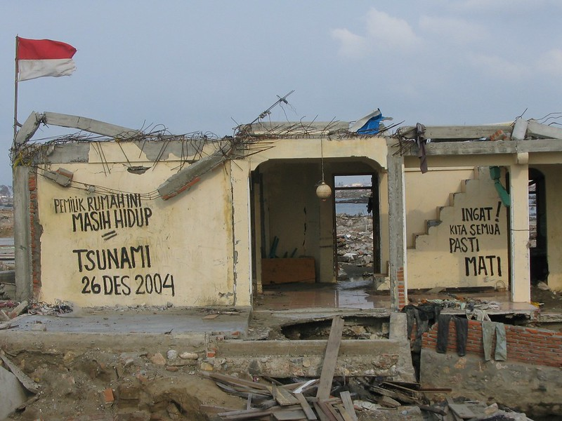 """A photograph of a cream coloured building that was partially destroyed by a tsunami in 2004. Large letters hand-written on the walls say """"Pemuk rumahini masih hidup. Tsunami 26 Des 2004. Ingat! Kita semua pasti mati."""" A red and white flag flies on the roof."""