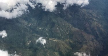 An aerial view of the highlands of Papua New Guinea. There are clouds in the foreground and far below buildings and narrow roads.