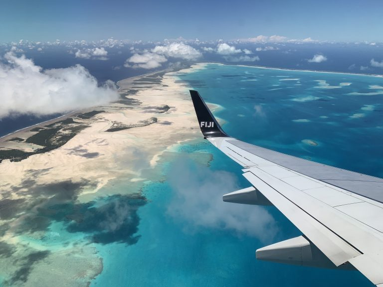 Image shows the view from an airplane over the wing. There are clouds in the mid distance and below there is the ocean in varying shades of blue, golden sands, and green vegetation.
