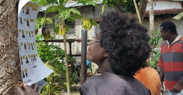 A women in Bougainville, Papua New Guinea, checks the photos and descriptions of candidates in the 2017 elections. The notice is attached to a tree. The woman has black curly hair and wears glasses. In the background is a thatched hut, a garden, and a man in a red and grey striped t-shirt.