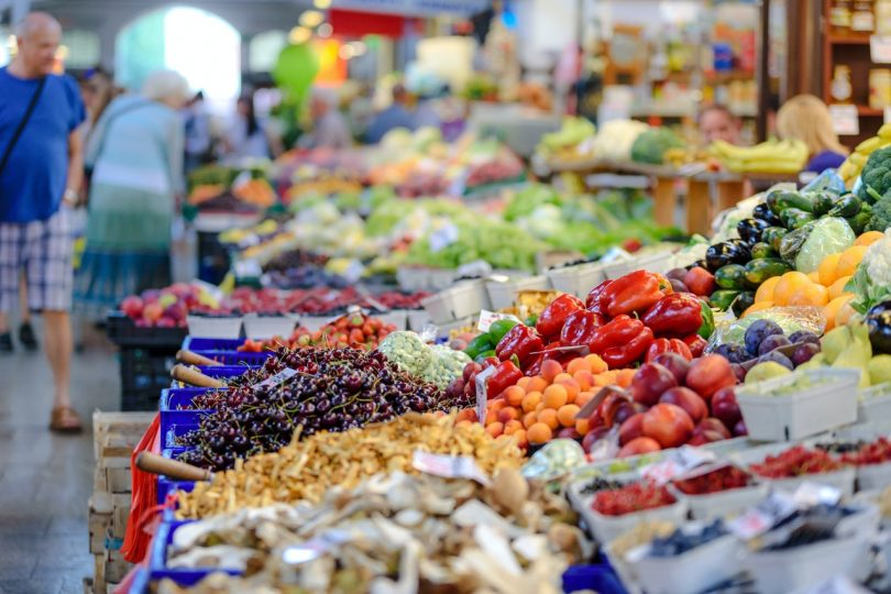 Photograph of a colourful display of fruits and vegetables in a store, including cherries, apricots, capsicums, plums, eggplant and broccoli.