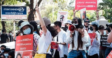 Photograph of people at a February 2021 protest agains the military coup in Myanmar. People are wearing masks and carrying signs. One woman holds a megaphone to her masked mouth.