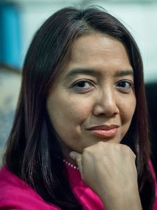 Close up photograph of Myanmar activist Thin Thin Aung. She has long dark hair, is wearing a pink top and has a silver watch on her wrist.