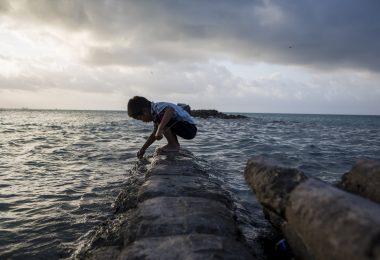 A boy plays on a flooded sea wall in Kiribati (Conor Ashleigh-World Bank)