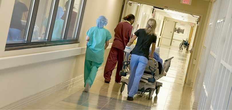 Photograph of a hospital corridor: ahead three hospital staff accompany a patient being moved on a bed.
