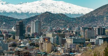 View of the city of Kabul with high rise buildings and snow-capped mountains in the distance.